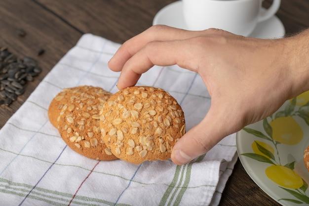 나무 테이블에 씨앗과 쿠키를 들고 남성 손.