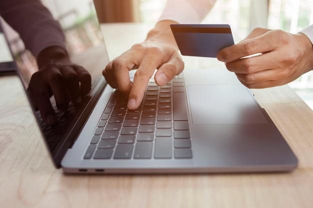 Мужская рука, держащая кредитную карту и использующая концепцию интернет-покупок ноутбука
