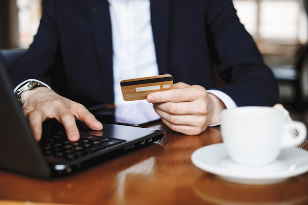 Male hand holding a credit card while operating at a laptop sitting at a desk drinking coffee.
