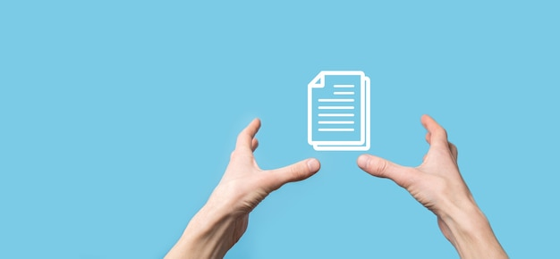Male hand holding a document icon on blue background. document management data system business internet technology concept. corporate data management system dms.
