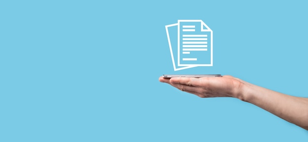 Male hand holding a document icon on blue background. document management data system business internet technology concept. corporate data management system dms