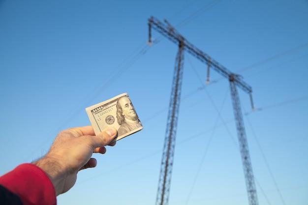 남성 손 고전압 전기 전송 타워 배경에 달러 지폐를 들고.