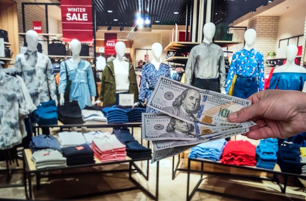 Male hand holding dollar in clothing store for purchase. cash