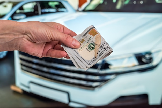 Male hand holding dollars in front of car Premium Photo