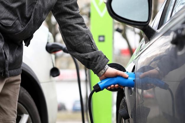 電気自動車のクローズアップを充電しながら電気ソケットを持っている男性の手