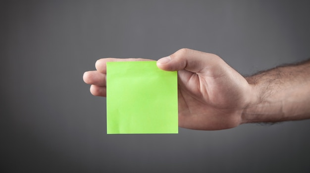 Male hand holding empty green sticky note.
