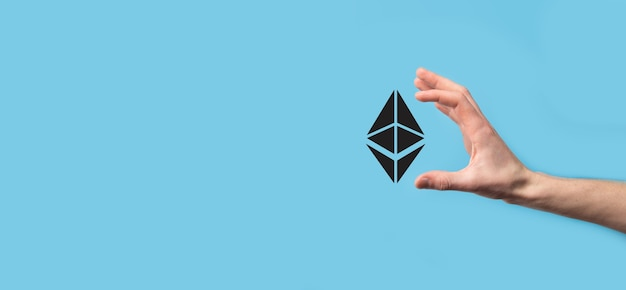 Male hand holding a ethereum icon on blue surface
