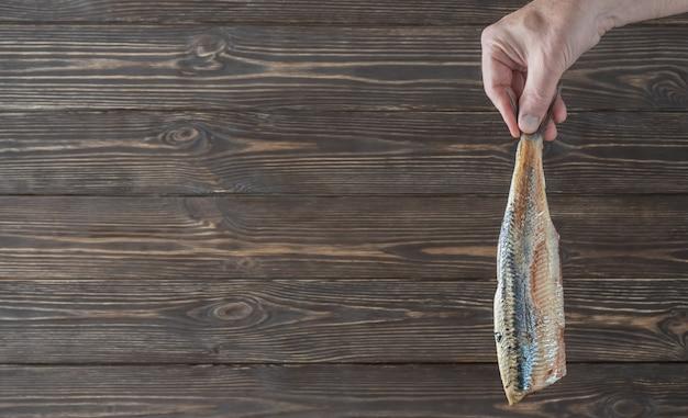 Male hand holding fillet of herring