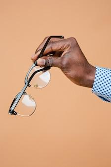 分離された眼鏡を持っている男性の手