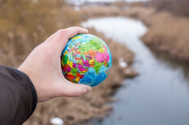 Male hand holding a globe of planet earth