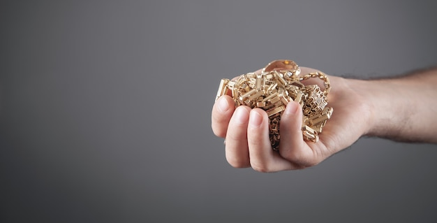 Male hand holding gold jewelry.