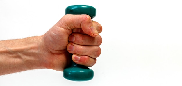Male hand holding green dumbbell isolated on white background. minimalistic concept.
