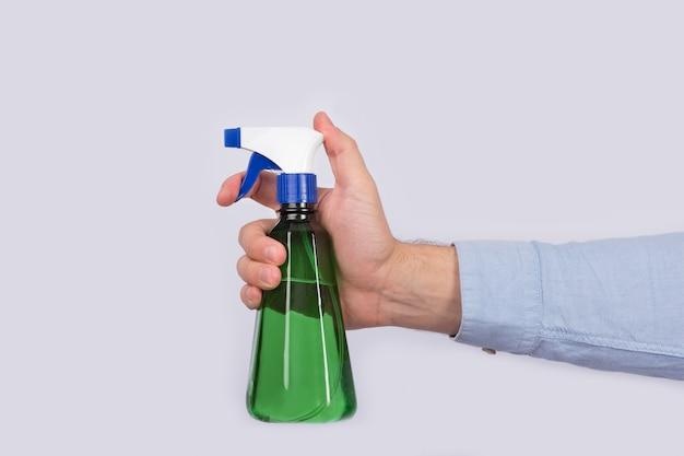 Male hand holding green spray bottle on white space. spray gun close up.