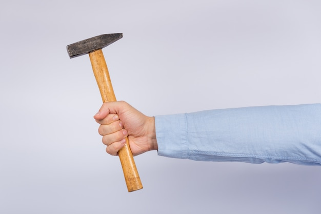 Male hand holding hammer on white.