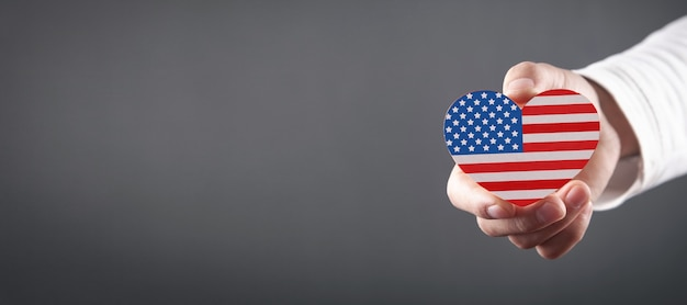 Male hand holding heart in the form of the usa flag.