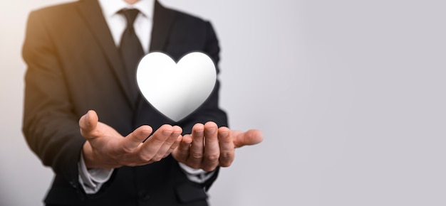 Male hand holding heart , like icon on blue background. kindness, charity, pure love and compassion concept.banner with copy space