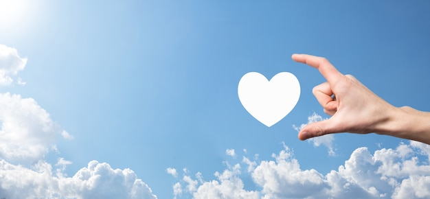 Male hand holding heart , like icon on blue background. kindness, charity, pure love and compassion concept.banner with copy space.
