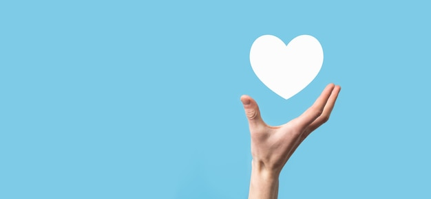 Male hand holding heart , like icon on blue background. kindness, charity, pure love and compassion concept.