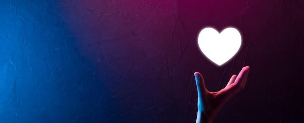 青い背景のアイコンのように、心を持っている男性の手。優しさ、慈善、純粋な愛と思いやりの概念。コピースペースのバナー