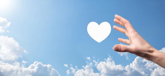 Мужская рука держит сердце, как значок на синем фоне. концепция доброты, милосердия, чистой любви и сострадания. баннер с копией пространства.