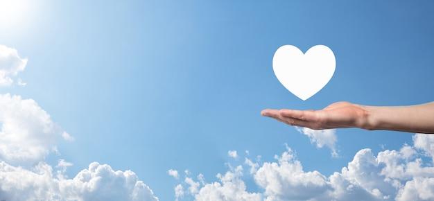 青い背景のアイコンのように、心を持っている男性の手。優しさ、慈善、純粋な愛と思いやりの概念。コピースペースのバナー。