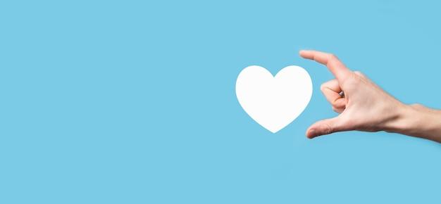 青い背景のアイコンのように、心を持っている男性の手。優しさ、慈善、純粋な愛と思いやりの概念。 Premium写真