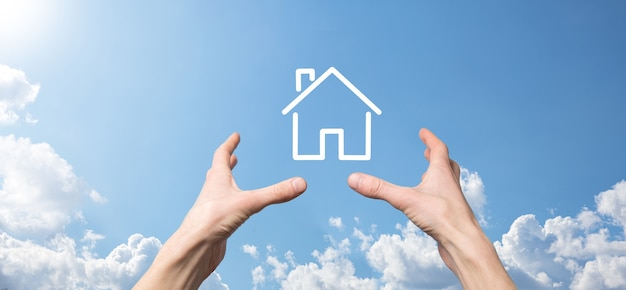 Male hand holding house icon on blue background. property insurance and security concept.real estate concept.banner with copy space.