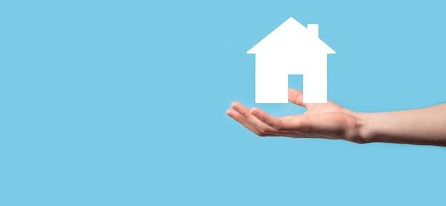 파란색 배경에 집 아이콘을 들고 남성 손입니다. 재산 보험 및 보안 개념입니다. 부동산 개념입니다. 복사 공간이 있는 배너입니다.