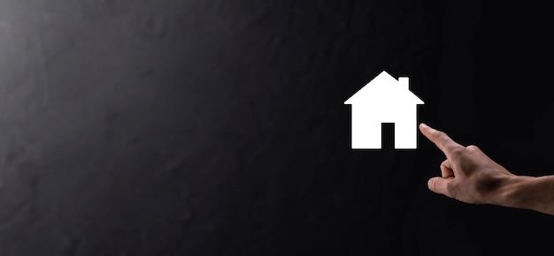 青い背景の上の家のアイコンを持っている男性の手。財産保険とセキュリティの概念。不動産の概念。コピースペース付きのバナー。