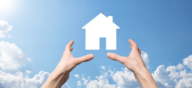 Мужской рукой, держащей значок дома на синем фоне. страхование имущества и концепция безопасности. концепция недвижимости. баннер с копией пространства.