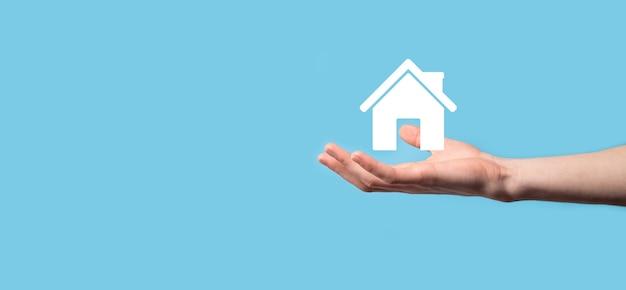 青い背景の上の家のアイコンを持っている男性の手。財産保険とセキュリティの概念。不動産の概念。