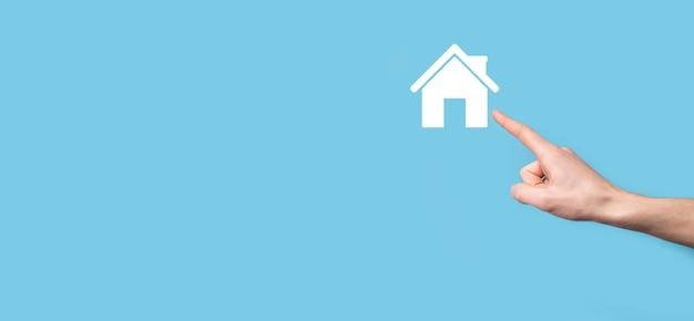 Мужской рукой, держащей значок дома на синем фоне. страхование имущества и концепция безопасности. концепция недвижимости.