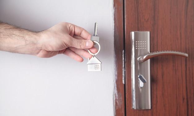 Мужской рукой, держащей ключ от дома дома.