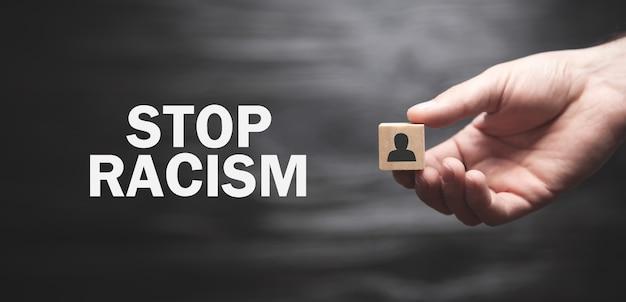 Мужская рука держит человеческую фигуру на деревянном кубе. остановить расизм