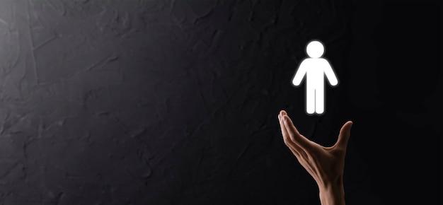 파란색 배경에 인간의 아이콘을 들고 남성 손입니다. 인적 자원 hr 관리 모집 고용 헤드헌팅 개념입니다. 팀 리더 개념을 선택합니다. 남성 손 남자 아이콘을 클릭합니다.배너, 복사 spase입니다.