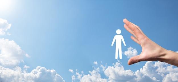 파란색 배경에 인간의 아이콘을 들고 남자 손입니다. 인적 자원 hr 관리 모집 고용 headhunting concept. 팀 리더 개념을 선택하십시오. 남성 손 남자 아이콘을 클릭합니다. 배너, 복사 spase.