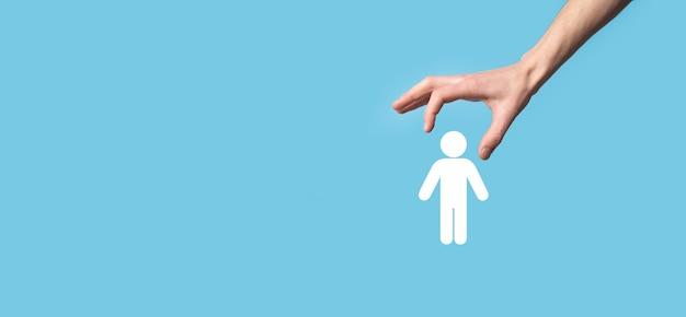 青い背景に人間のアイコンを保持している男性の手