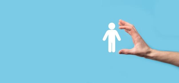 青い背景に人間のアイコンを保持している男性の手。