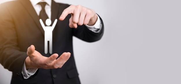 灰色の背景に人間のアイコンを持っている男性の手。人的資源人事管理採用雇用ヘッドハンティングの概念。チームリーダーの概念を選択します。男性の手は男性のアイコンをクリックします。バナー、コピーspase。