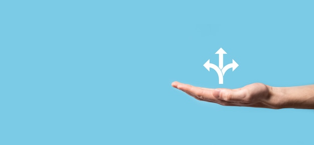 파란색 배경에 세 방향 아이콘이있는 남성 손 잡고 아이콘 .n 의심, 화살표로 표시된 세 가지 선택 중에서 선택해야 함