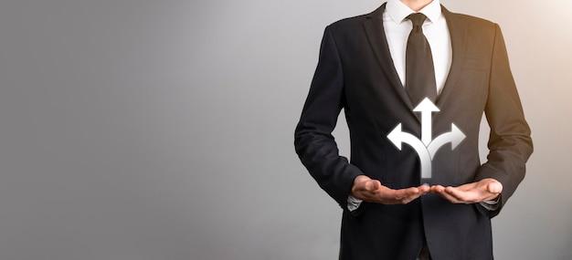 暗い背景の上の3つの方向のアイコンとアイコンを持っている男性の手。疑い、反対方向の概念を指す矢印で示される3つの異なる選択肢から選択する必要があります。方法