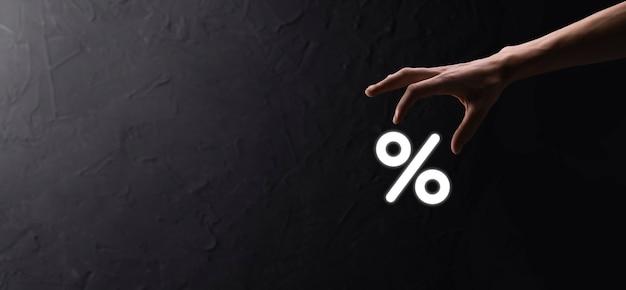파란색 배경에 이자율 퍼센트 아이콘을 들고 있는 남성 손. 금리 금융 및 모기지 금리 개념입니다. 복사 공간이 있는 배너