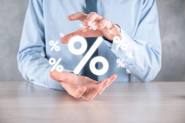 파란색 배경에 이자율 퍼센트 아이콘을 들고 있는 남성 손. 금리 금융 및 모기지 금리 개념입니다. 복사 공간이 있는 배너 프리미엄 사진