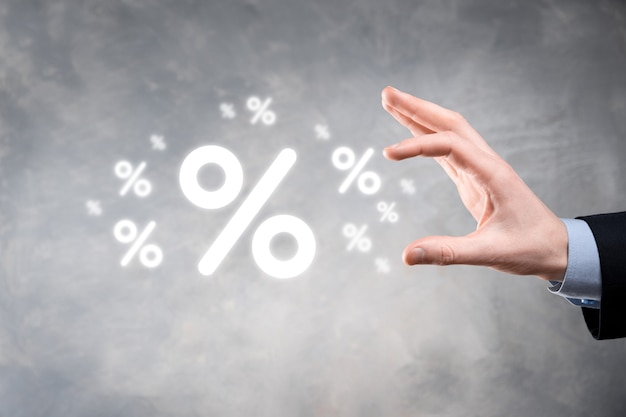 Мужская рука, держащая значок процента процентной ставки на синем фоне. концепция финансовых и ипотечных ставок процентной ставки. баннер с копией пространства