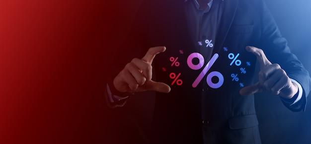 Мужская рука, держащая значок процента процентной ставки на синем фоне. концепция финансовых и ипотечных ставок процентной ставки. баннер с копией пространства.