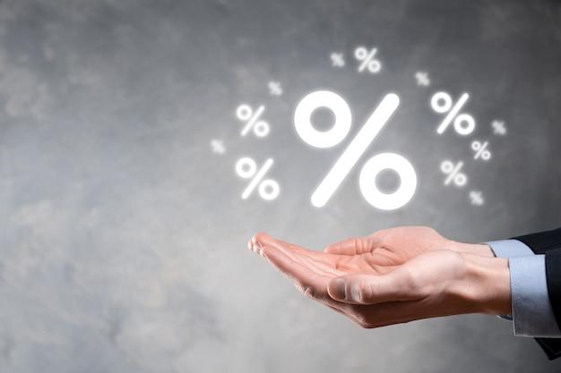 Мужская рука, держащая значок процента процентной ставки на синем фоне. концепция финансовых и ипотечных процентных ставок. баннер с копией пространства