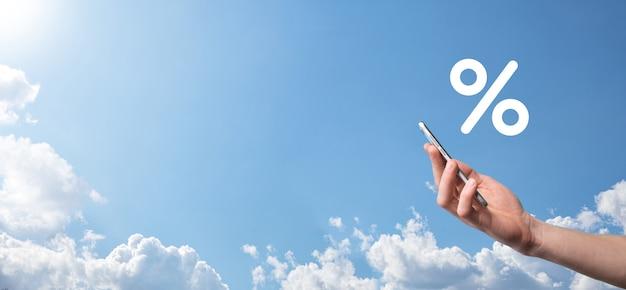 青い空を背景に金利パーセント アイコンを持っている男性の手。金利の金融と住宅ローンの金利の概念。コピー スペースを持つバナー。