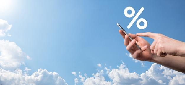 푸른 하늘 배경에 금리 % 아이콘을 들고 남자 손. 금리 금융 및 모기지 금리 개념 복사 공간 배너입니다.