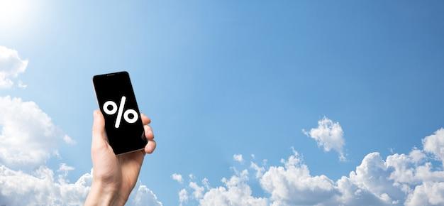 Мужская рука, держащая значок процента процентной ставки на фоне голубого неба. концепция финансовых и ипотечных ставок процентной ставки. баннер с копией пространства.