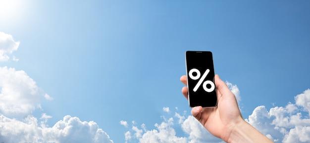 Мужская рука, держащая значок процента процентной ставки на фоне голубого неба. концепция финансовых и ипотечных процентных ставок. баннер с копией пространства